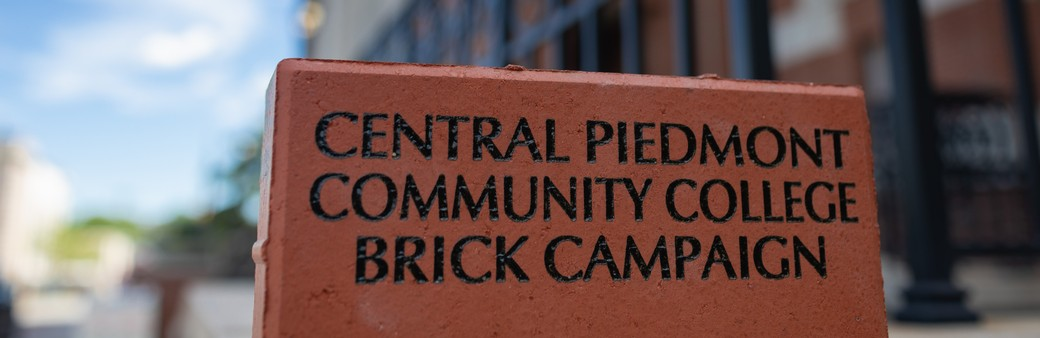brick building in background with single brick in foreground engraved central piedmont community college brick campaign