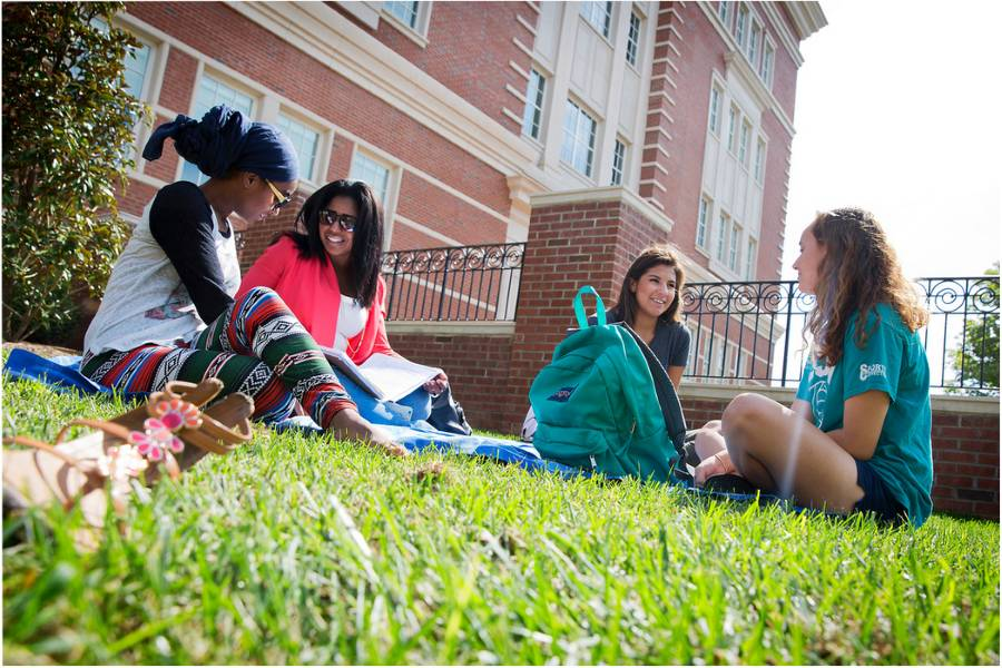 female students sitting in grass