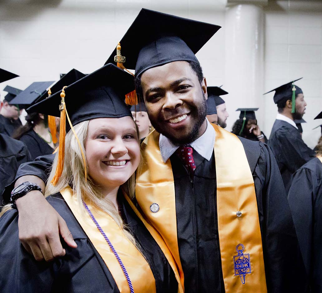 Two graduates in cap and gown